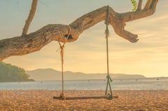 Hölzerner Schwingenstuhl nahe dem Ozeansonnenuntergang, chonburi, Thailand Lizenzfreie Stockbilder