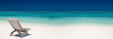 Hölzerner Segeltuchstuhl auf einem schönen tropischen Strand Lizenzfreie Stockbilder