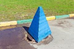 Hölzerner Sicherheitskegel steht auf einem Abwasserkanaleinsteigeloch Stockfotos