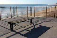 Hölzerner Sitz, der den Ozean übersieht Lizenzfreie Stockfotos
