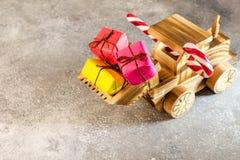 Hölzerner Spielzeugtraktor trägt Weihnachtsgeschenke in seinem Eimer E Lizenzfreie Stockfotografie