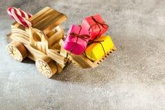 Hölzerner Spielzeugtraktor trägt Weihnachtsgeschenke in seinem Eimer E Stockfotos