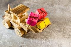 Hölzerner Spielzeugtraktor trägt Weihnachtsgeschenke in seinem Eimer E Stockbild