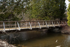 Hölzerner Steg im Park, der den Fluss an einem Frühlingstag kreuzt Stockbild