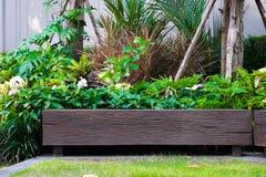Hölzerner Stuhl im Garten, Ansicht des Gartenpatios stockbild