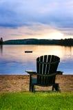 Hölzerner Stuhl am Sonnenuntergang auf Strand Lizenzfreie Stockfotos