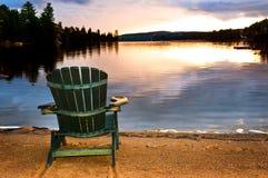 Hölzerner Stuhl am Sonnenuntergang auf Strand Lizenzfreies Stockfoto