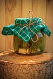 Hölzerner Stumpf der in Essig eingelegten Gurken des Glases Stockfotografie