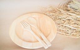Hölzerner Tellersatz und ungeschälter Reis Lizenzfreies Stockbild
