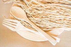 Hölzerner Tellersatz und ungeschälter Reis Stockbilder
