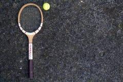 Hölzerner Tennisschläger der alten Weinlese auf lokalisiertem Steinhintergrund mit grünem Ball Stockbilder
