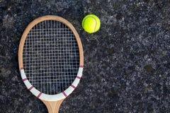 Hölzerner Tennisschläger der alten Weinlese auf lokalisiertem Steinhintergrund mit grünem Ball Stockfotografie