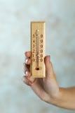 Hölzerner Thermometer in der Hand Stockbilder