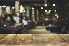 Hölzerner Tischplatte-Zähler mit verwischt von der Kaffeestube oder von der modernen Bibliothek stockfotografie