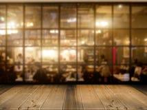 Hölzerner Tischplattezähler mit Nachtcafé-Clubhintergrund lizenzfreie stockfotografie