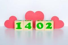 Hölzerner Würfel mit Aufschrift am 14. Februar und rote Herzen formen Lizenzfreie Stockfotografie