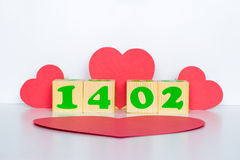 Hölzerner Würfel mit Aufschrift am 14. Februar und rote Herzen formen Stockbild