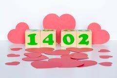 Hölzerner Würfel mit Aufschrift am 14. Februar und rote Herzen formen Lizenzfreies Stockbild