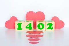 Hölzerner Würfel mit Aufschrift am 14. Februar und rote Herzen formen Lizenzfreie Stockfotos