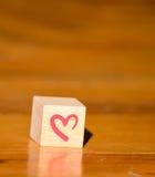 Hölzerner Würfel mit einer Hand rotes Herz geschrieben Lizenzfreies Stockfoto