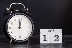 Hölzerner Würfelformkalender für den 12. April mit schwarzer Uhr Stockbild