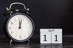 Hölzerner Würfelformkalender für den 11. April mit schwarzer Uhr Stockfotos