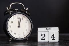 Hölzerner Würfelformkalender für den 24. April mit schwarzer Uhr Stockfotografie