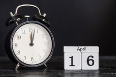 Hölzerner Würfelformkalender für den 16. April mit schwarzer Uhr Lizenzfreie Stockfotografie