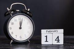 Hölzerner Würfelformkalender für den 14. Februar mit schwarzer Uhr Stockfotos