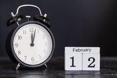 Hölzerner Würfelformkalender für den 12. Februar mit schwarzer Uhr Stockfotografie