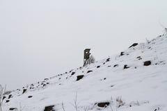 Hölzerner Wachturm auf schneebedecktem Hügel Stockbild