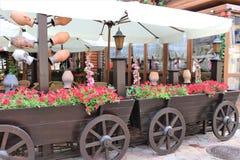 Hölzerner Wagen mit roten Blumen Dekorativer Lastwagen im Freien mit Blumen und keramischen amphorae lizenzfreie stockfotos
