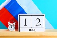Hölzerner weißer Kalender mit dem Datum vom 12. Juni vor dem hintergrund der Flagge von Russland Russland-Tag Lizenzfreie Stockfotografie