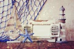 Hölzerner weißer Rahmen, Leuchtturm, Starfish und Segelboot der alten Weinlese auf Holztisch Weinlese gefiltertes Bild Seelebenss Stockbilder