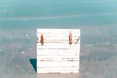 Hölzerner weißer Rahmen mit Clip für hängenden Anmerkungsfotomitteilungsseefeiertags-Naturhintergrund stockbilder