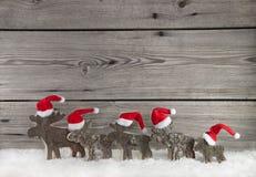 Hölzerner Weihnachtshintergrund mit einer Gruppe von Weihnachtsmann auf Holz Stockfoto