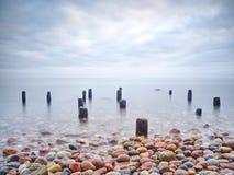 Hölzerner Wellenbrecher im ruhigen Abendmeer Reine romantische Atmosphäre stockfoto