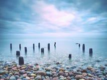 Hölzerner Wellenbrecher im ruhigen Abendmeer Reine romantische Atmosphäre stockbilder