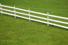 Hölzerner Zaun auf einem grünen Rasen Lizenzfreie Stockbilder