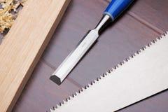 Hölzerner Ziegelstein, Meißel und Handsaw auf dem Fußboden Lizenzfreie Stockfotografie