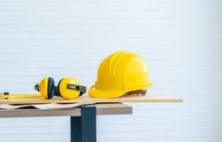 Hölzernes Arbeitsgerät mit Kopfhörergehörschutz auf einer Tabelle stockbilder