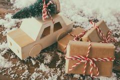 Hölzernes Auto, das eine Kiefer nahe bei den Weihnachtsgeschenken transportiert Lizenzfreie Stockbilder