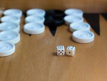 Hölzernes Backgammonbrett mit weißen Schlitzen und Würfeln Stockbilder