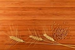 Hölzernes Bambusschneidebrett mit drei Weizenähren und Körnern Lizenzfreies Stockfoto