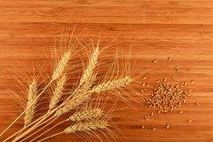 Hölzernes Bambusschneidebrett mit neun Weizenähren und Körnern Lizenzfreies Stockbild