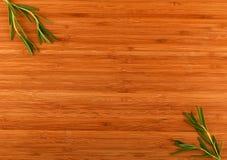 Hölzernes Bambusschneidebrett mit Rosmarinblättern Stockfoto