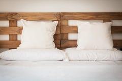 Hölzernes Bett mit weißem Leinen Stockbilder
