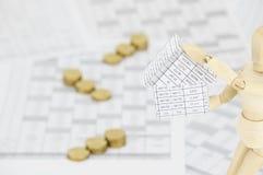 Hölzernes blindes haltenes Haus haben UnschärfeGoldmünzen als Hintergrund Lizenzfreies Stockfoto