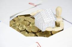 Hölzernes blindes haltenes Haus umgeben durch Goldmünzen und Schreibarbeit Lizenzfreie Stockbilder