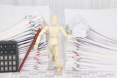 Hölzernes blindes haltenes Haus und Bleistift zwischen Doppelüberlastungsdokument Stockbilder
